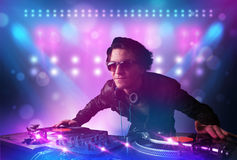 Disc jockey mixing music on turntables on stage with lights and. Young disc jockey mixing music on turntables on stage with lights and stroboscopes Stock Images