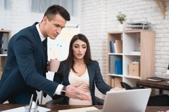 Young disgruntled man in suit scolds pregnant girl for mistakes in work done. stock photos