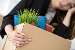 Young dismissed female worker in office holding carton box with Royalty Free Stock Image