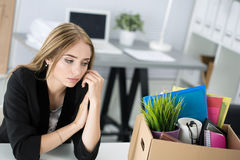 Young dismissed female worker in office sitting near carton box stock photos