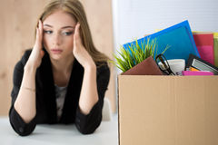 Young dismissed female worker sitting near the carton box with h Royalty Free Stock Photo