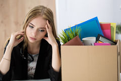 Young dismissed female worker sitting near the carton box with h Stock Photo