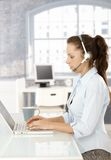 Young dispatcher working in bright office. Using laptop and headphones, typing royalty free stock photos