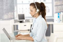 Young dispatcher working in bright office. Using laptop and headphones, typing Royalty Free Stock Images