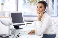 Young dispatcher working in bright office smiling. Attractive young dispatcher working in bright office, sitting at desk, smiling Stock Photos