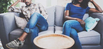 Young displeased black couple.American african men arguing with his stylish girlfriend,who is sitting on sofa on couch. Next to him with legs crossed.Man stock photo