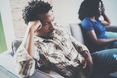 Young displeased black couple.Upset man being ignored by partner at home in the living room.American african men arguing. Young displeased black couple.Upset men royalty free stock images