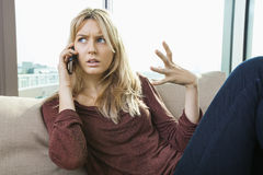 Young displeased woman talking on mobile phone at home Royalty Free Stock Photography