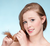 Young displeasure woman with hair ends. Close up portrait of young displeasure woman that comb perfect hair Stock Image
