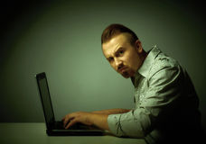 Young dissatisfied man working with laptop. Royalty Free Stock Photography