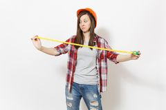 Young dissatisfied woman in casual clothes, protective construction helmet holding toy measure tape isolated on white. Background. Instruments, tools for stock photos