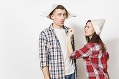 Young dissatisfied woman, man in casual clothes and newspaper hats quarrelling. Couple isolated on white background royalty free stock photo