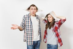 Young dissatisfied woman, man in casual clothes and newspaper hats spreading hands. Couple isolated on white background stock photography