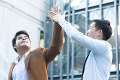 Young Diverse Asian Business Men Giving High Five Royalty Free Stock Photography