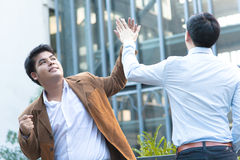 Young Diverse Asian Business Men Giving High Five Royalty Free Stock Images