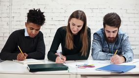 Young diverse multi-ethnic students writing an exam at school or university. Test at school. Slowmotion shot.  stock footage