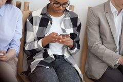 Young diverse people sitting in chair using smartphones stock photos
