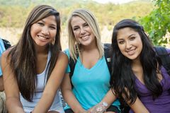 Young Diverse Woman. Racially diverse group of American college aged young women taking a break from hiking on a summer day Stock Image
