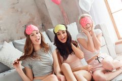 Slumber Party. Young women in sleeping mask together at home sitting on floor smiling playful close-up stock photography
