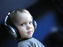 Young DJ 1. Protrait of a little boy with headphones listening to music, suspecting expression on his face Stock Images