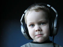 Young DJ 2. Young boy listening music with huge earphones. Almost funny Royalty Free Stock Image