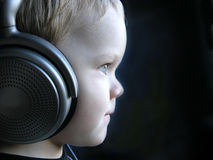 Young DJ 3. Young boy listening music with huge earphones. Almost funny. Sharpest focus is on the earpiece in this one Stock Photos