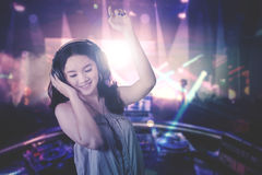 Young DJ dancing in the nightclub. Image of a beautiful young DJ playing music while dancing in the night club Stock Photos