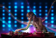 Young Dj girl mixing records with colorful lights. Beautiful young Dj girl mixing records with colorful lights Royalty Free Stock Image