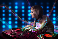 Young Dj girl mixing records with colorful lights Royalty Free Stock Image