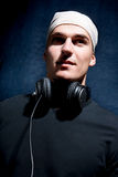 A young DJ  is listening to music. On his headphones! Isolated blue background Stock Photo