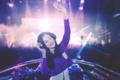 Young DJ looks happy. Image of a young DJ looks happy while playing her song for people in the nightclub Royalty Free Stock Photos