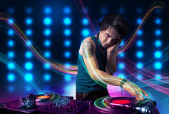 Young Dj mixing records with colorful lights. Attractive young Dj mixing records with colorful lights Royalty Free Stock Photo