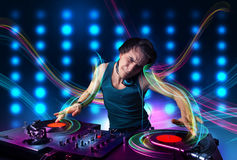 Young Dj mixing records with colorful lights Stock Images