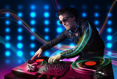 Young Dj mixing records with colorful lights Stock Photos