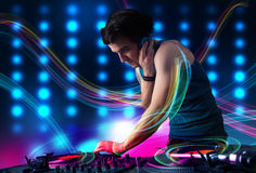 Young Dj mixing records with colorful lights. Attractive young Dj mixing records with colorful lights Royalty Free Stock Images