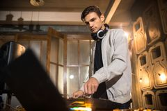 Young DJ Playing in Club. Side view portrait of trendy young DJ playing music using mixer and looking at laptop screen in  night club party, copy space Royalty Free Stock Images