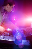 Young DJ playing records at a party in a nightclub. Royalty Free Stock Images
