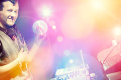 Young DJ playing records at a party in a nightclub. Royalty Free Stock Photography