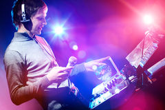 Young DJ playing records at a party in a nightclub. Royalty Free Stock Image