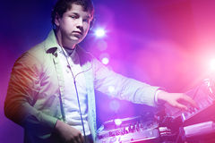 Young DJ playing records at a party in a nightclub. Stock Images
