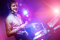 Young DJ playing records at a party in a nightclub. Stock Photography