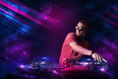 Young DJ playing on turntables with color light effects royalty free illustration