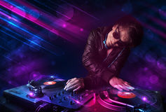 Young DJ playing on turntables with color light effects Stock Images