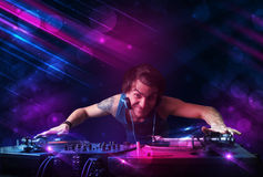 Young DJ playing on turntables with color light effects Royalty Free Stock Photos
