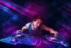Young DJ playing on turntables with color light effects Royalty Free Stock Image