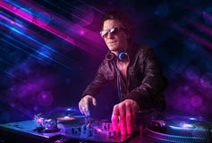 Young DJ playing on turntables with color light effects. Attractive young DJ playing on turntables with color light effects Stock Photo