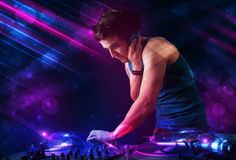 Young DJ playing on turntables with color light effects Stock Photos
