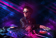 Young DJ playing on turntables with color light effects Royalty Free Stock Photography