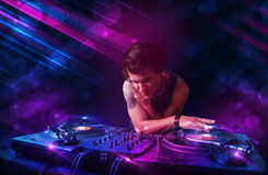 Young DJ playing on turntables with color light effects Stock Photography