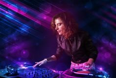 Young DJ playing on turntables with color light effects. Beautiful young Dj playing on turntables with color effects Royalty Free Stock Images